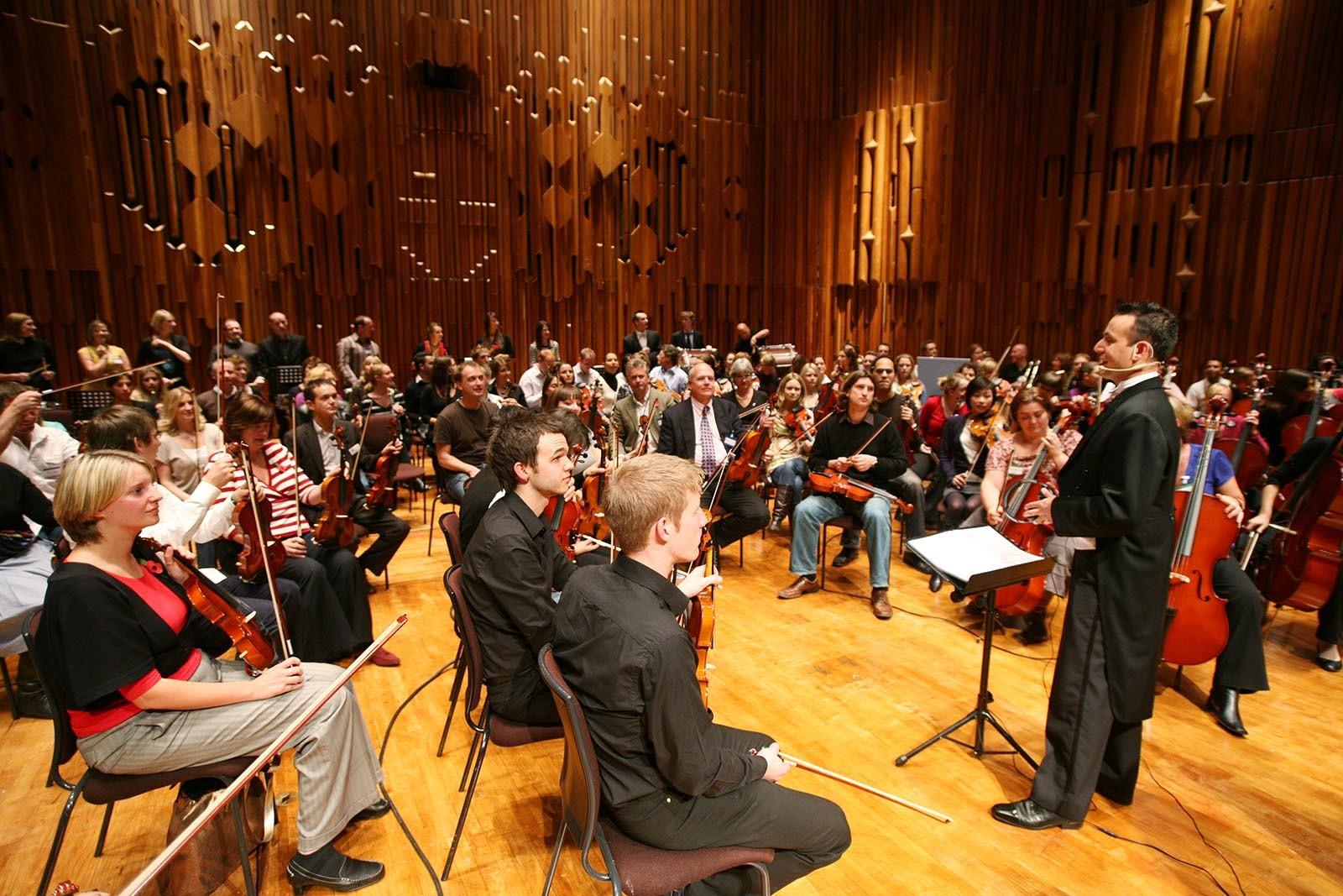 Hudebni dirigent vysvetluje ucastnikum jaka prace je za sestavenim orchestru pri hre Orchestrate