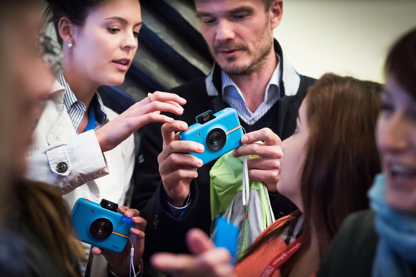 Moderatorka ukazuje ucastnikum hry Photopoly jak zachazet s polaroidem