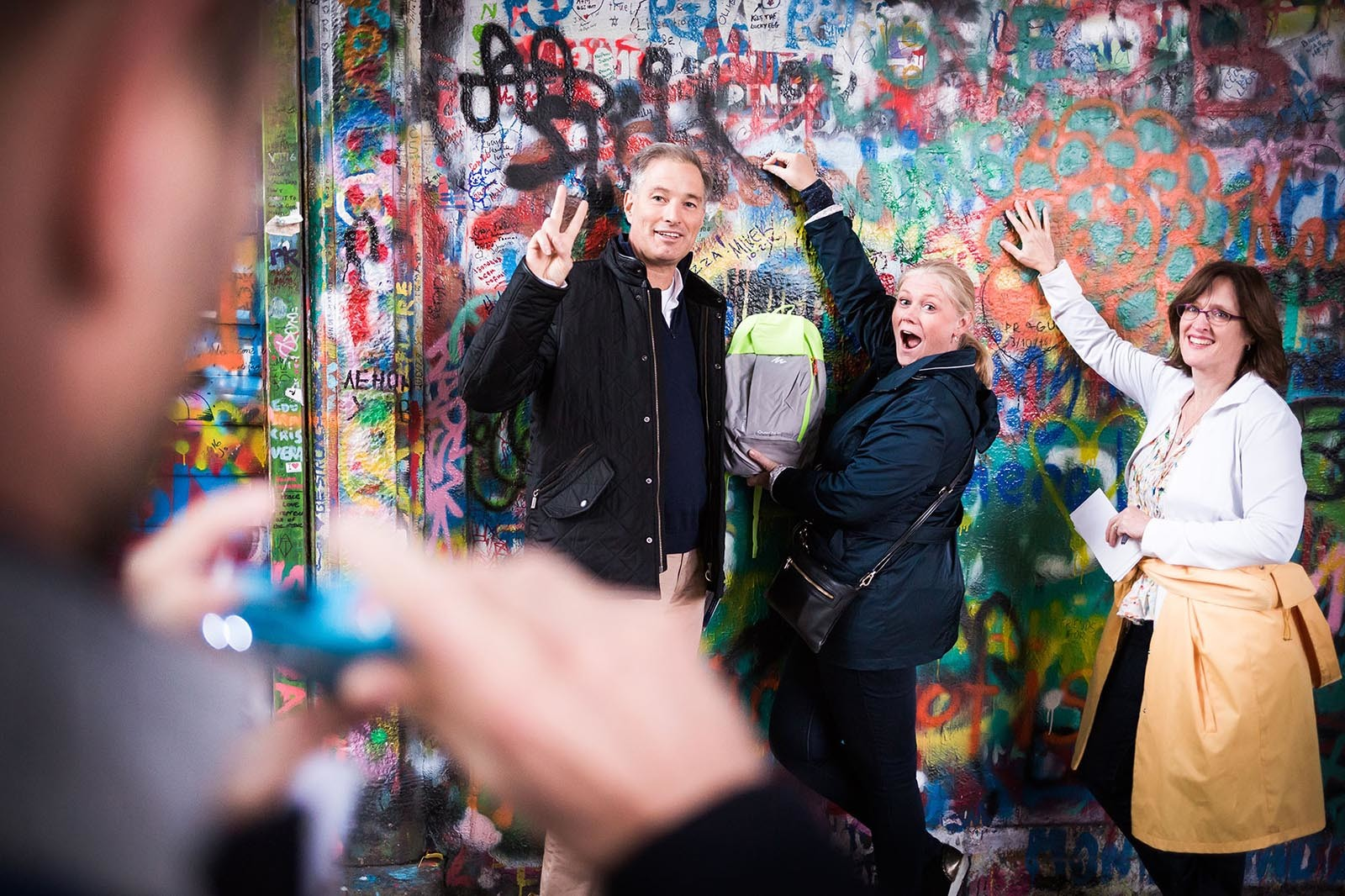 Skupinka lidi se foti u Lennonovy zdi pri hre Photopoly